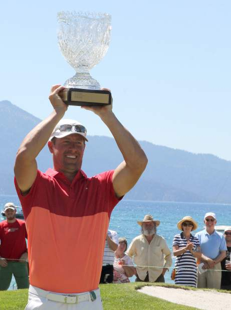 Mulder hoists the trophy after winning the American Century Championship on Sunday.
