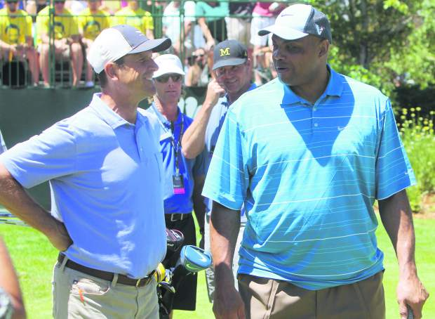 Michigan head coach Jim Harbaugh and NBA Hall of Famer Charles Barkley have a chat at the first hole Thursday.