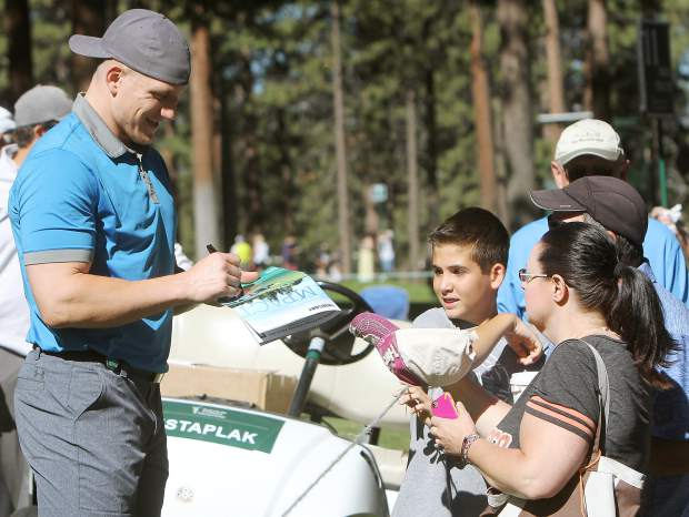 NFL linebacker A.J. Hawk signs for fans off the 11th tee box Thursday.