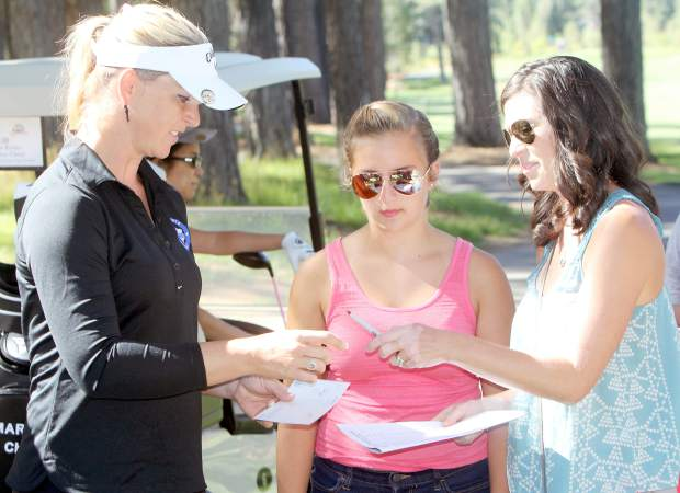 Long drive champion Heather LeMaster signs an autograph for a pair of female fans at the eighth tee box Tuesday.