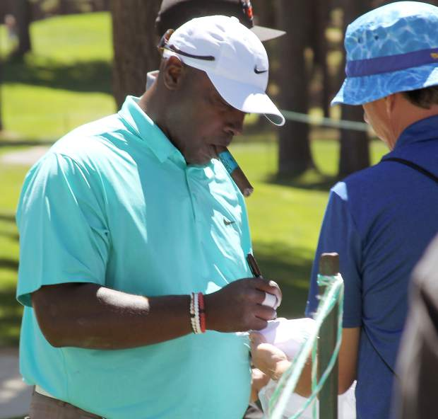 NFL Pro Bowler Sterling Sharpe puts pen to paper with a cigar in his mouth off the 16th green Tuesday.