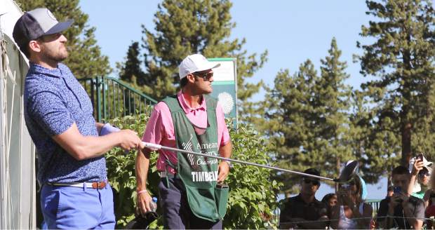 Justin Timberlake watches his tee shot on the first hole Wednesday while the gallery grabs shots of him.