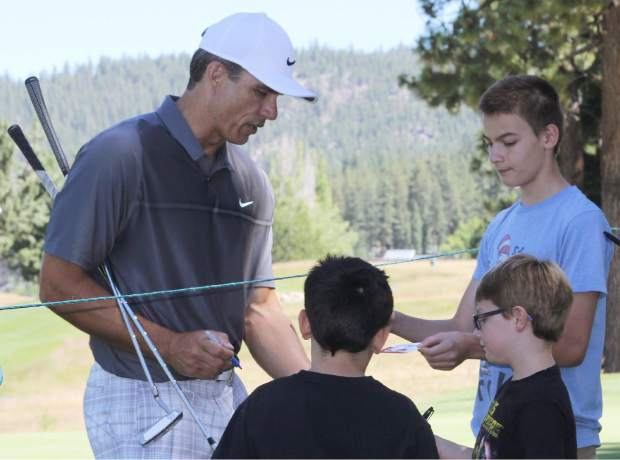Former NFL quarterback Trent Green signs an autograph for young fans on the fifth hole Wednesday.