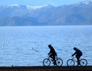 Bicyclists ride near the lake Wednesday afternoon at Camp Richardson.