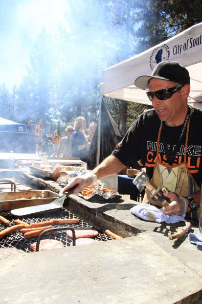 A volunteer cooks up free burgers and hot dogs at the South Lake Tahoe 50th anniversary celebration, Saturday, Sept. 19.
