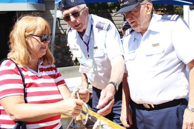Sharon Trentino (left) takes some pointers on how to tie a note from South Lake Tahoe Coast Guard Auxiliary officers Jim Snell (middle) and Dale Herman during the South Tahoe Wooden Boat Classic at the Tahoe Keys Marina on Saturday.