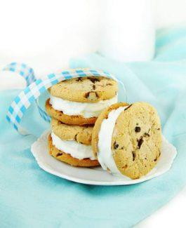 Chocolate chip cookie and ice cream sandwiches on blue and white background.