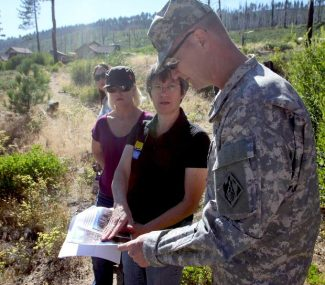 Penny Stewart, of the California Tahoe Conservancy, shows Col. Michael Farrell, of the U.S. Army Corps of Engineers, photos of an area effected by the Angora Fire. Farrell stood at the site during a tour around Lake Tahoe on Monday.