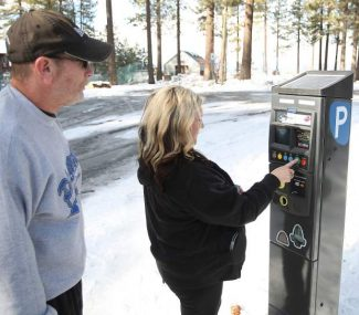 Local Mark Meurrens and Bay Area resident Mynette Boykin pay for parking in South Lake Tahoe earlier this month.