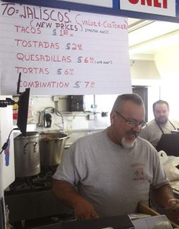 Manuel Zepeda, owner of Taqueria Jalisco in South Lake Tahoe, rings a customer up Thursday.  The sign above him is to inform patrons of a price change for certain menu items — a result of the California drought.