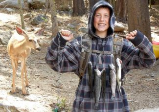 Brandon Browning, 13, of Carson City, Nev., holds up his limit of five fish while a deer sneaks up to eye the catch at Upper Twin Lake in Bridgeport, Calif., on Aug. 8. This was Browning and Grandpa Chuck Bonas' last outing before school starts. Browning was unaware of the doe behind him when the picture was taken. The day was topped by a bald eagle swooping across the lake for some fishing of its own.