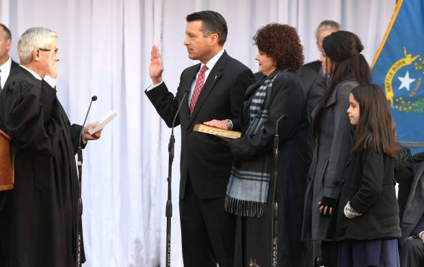 Gov. Brian Sandoval, joined by First Lady Kathleen Sandoval and daughters Maddy and Marisa takes the oath of office for his second term on Monday.