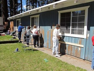 South Lake Tahoe Habitat for Humanity volunteers preparing a local house for painting.