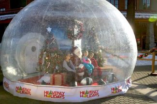A family takes a picture with Santa in a snow globe at Heavenly Village on Friday.
