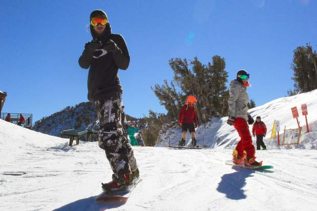 A snowboarder poses for the camera after buckling in for an opening day run at Heavenly Mountain Resort.