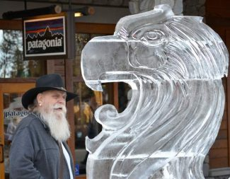 Los Angeles resident Richard Dominick stands next to a statue of an eagle's head at Heavenly Village on Monday.