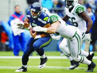 Seattle Seahawks quarterback Russell Wilson (3) is pulled down by New York Jets' Garrett McIntyre on Nov. 11, 2012, in Seattle. McIntyre, a South Tahoe alum, resigned with the Jets.