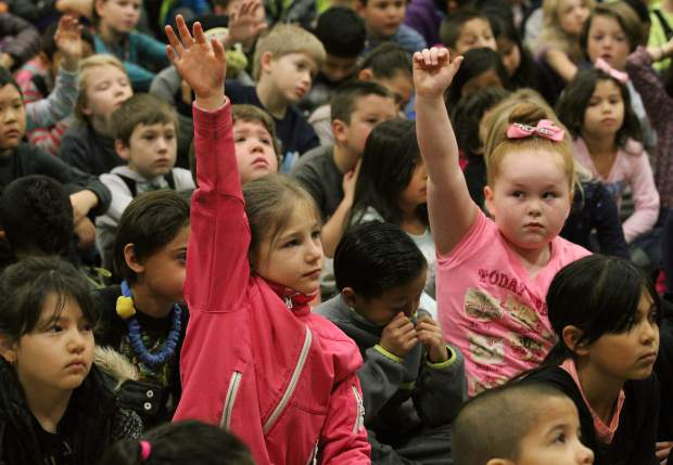 Second graders Ellie Cox Harrison (left) and Masie Underwood raise their hands to ask OpenSnow.com weather forecaster Bryan Allegretto a question during a school assembly at Sierra House Elementary.