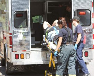 An emergency medical crew hoists the driver of a motorcycle into an ambulance Thursday after a crash on Emerald Bay Road.
