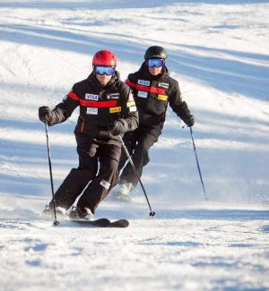 Dr. Jonathan Finnoff, left, and Dr. Terrence Orr ski down a mountain.