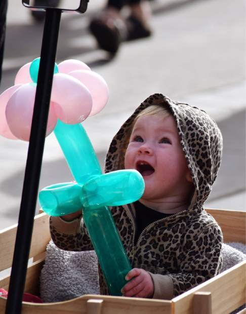 An infant plays with a balloon flower.