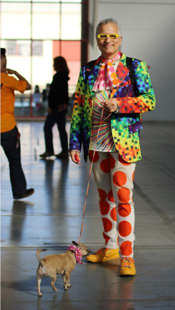 A colorfully dressed man walks his dog.