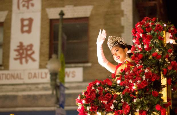 A parade participant waves from a float during Chinese New Year celebrations in San Francisco.