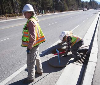 Tony Brackett, left, checks for traffic while Wayne Whittlesey watches Jon Root measure down to the inlet of a manhole. On Wednesday, the Caltrans survey crew was checking the drainage systems on Highway 50.