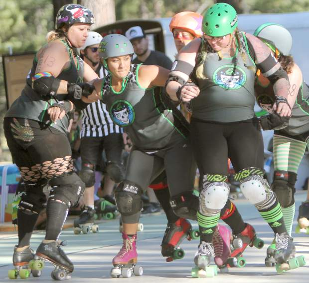 Led by Vette the Threat (middle), Derby Dames form a wall to block a Woodland jammer Saturday.