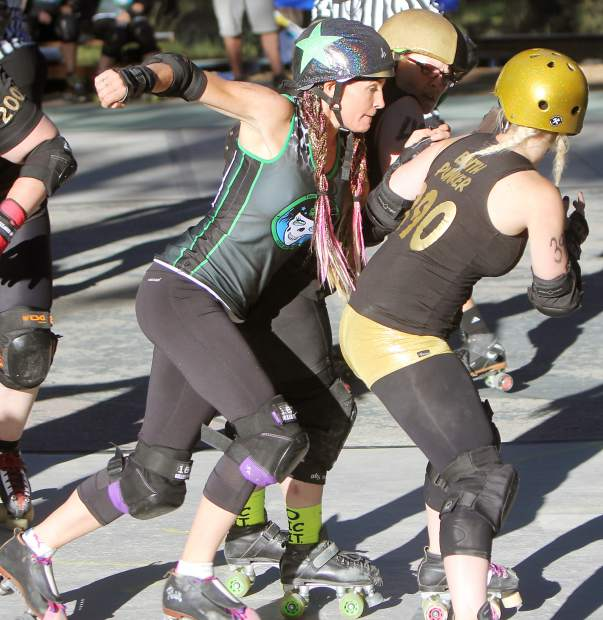 Derby Dames skater Passion SwivelHips tries to squeeze through a pair of Victory Rollers skaters Saturday.