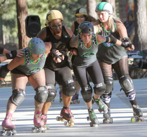 Tahoe Derby Dames skaters (left to right) Vette the Threat, Slayer and Ima Ryder seal off a Carson Victory Rollers opponent Saturday, July 16, at Bijou Community Park.