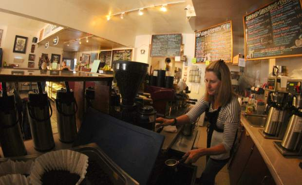 Rude Brothers co-owner Lisa Gosh prepares a morning coffee in their Harrison Avenue location.