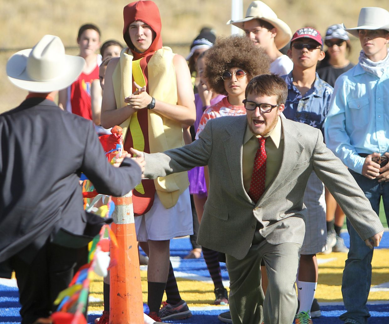 A suit-wearing runner tags up for the second leg of a relay with a hot dog and flower child waiting in the wings Tuesday.