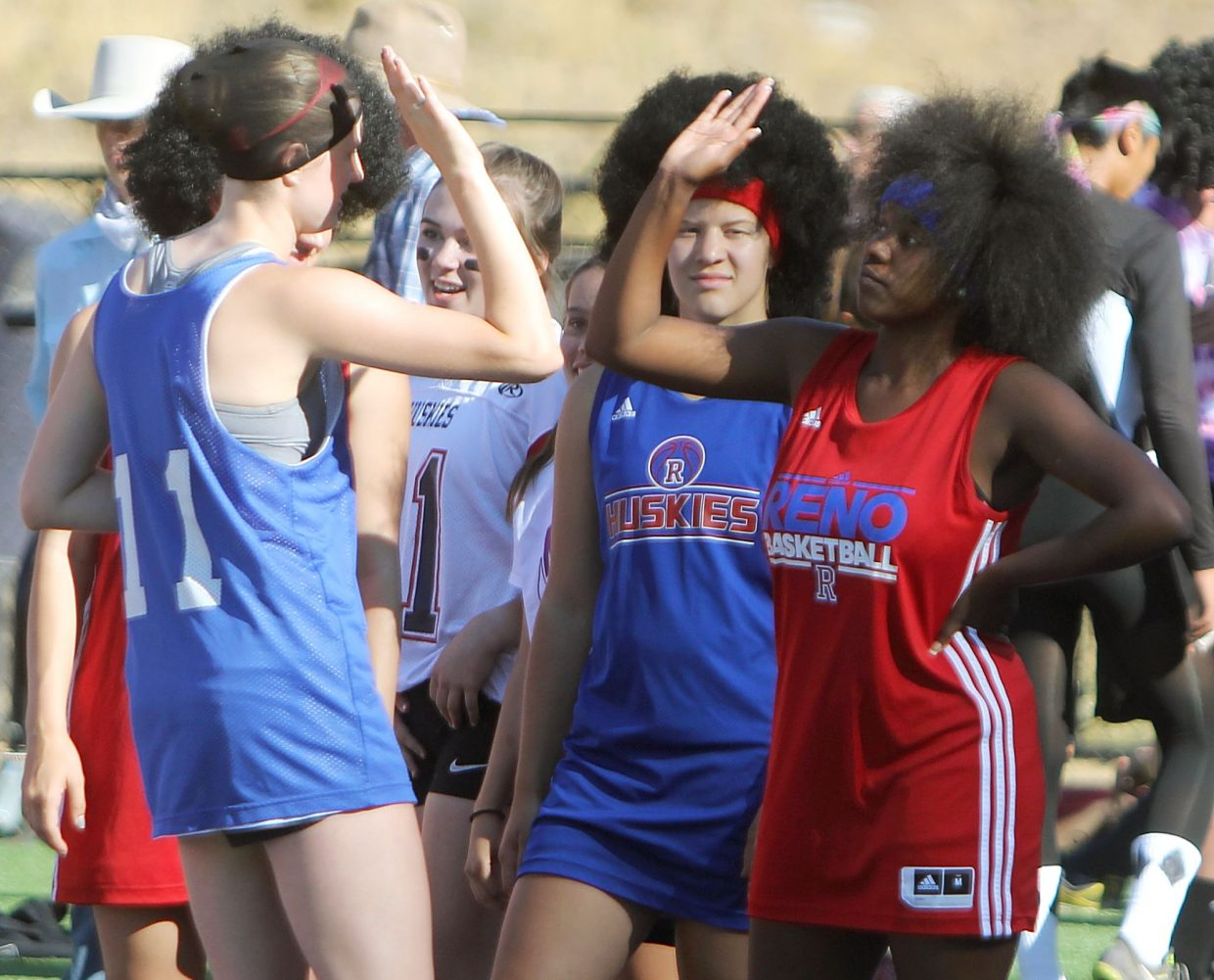 A duo of big-hair runners from Reno exchanges a high five at the start line Tuesday.