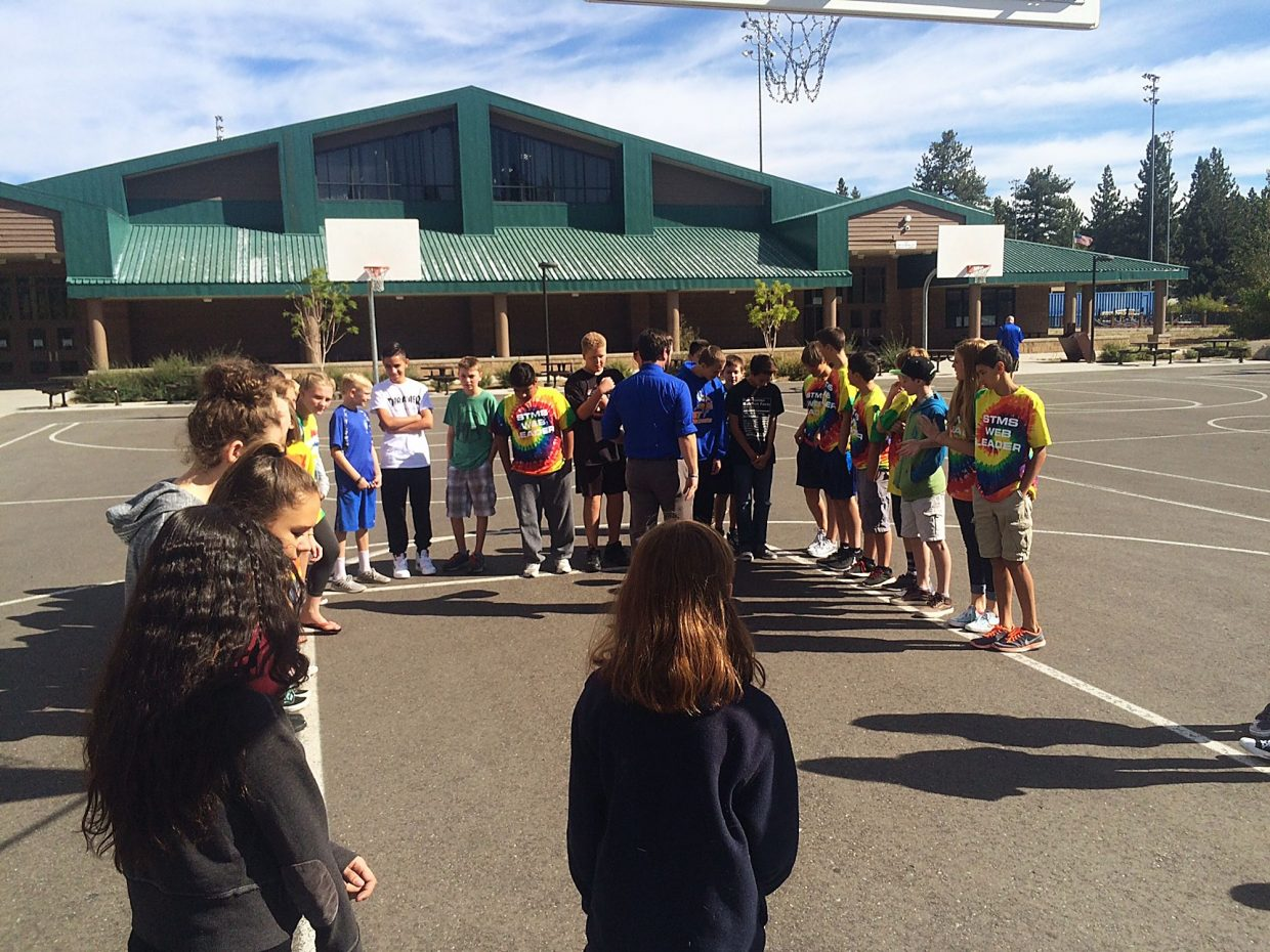 A group of South Tahoe Middle School WEB students listen to instructions outdoors.