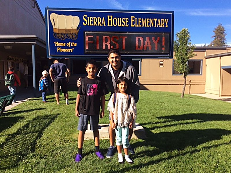 Many families posed for a photo in front of the school sign at Sierra House Elementary School on the first day of classes.