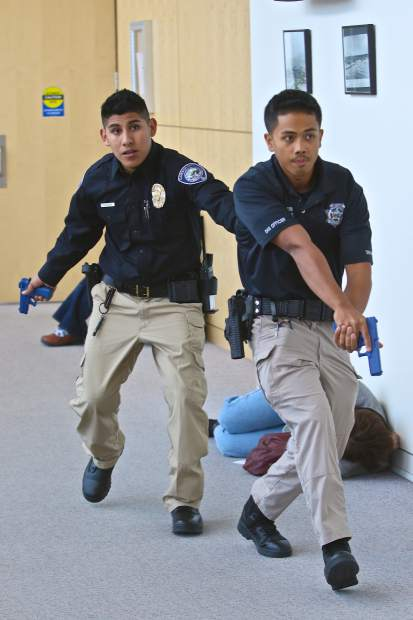 Department of Alternative Sentencing officers Sam Ugalde and Chris Ballesteros work their way down a hallway in the process of eliminating the 'shooter' threat on Sunday.