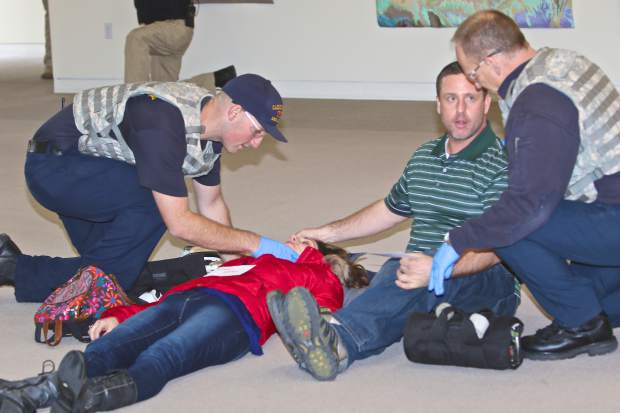 EMS personnel tend to gunshot wound victims Sandy Goins (red jacket) and Jeremy Saposnek (green shirt) as part of a training exercise at the Carson City Courthouse Sunday.