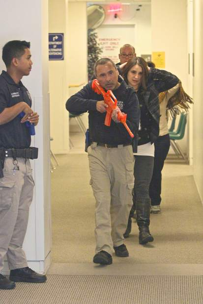Department of Alternative Sentencing officer Julio Lopez (with orange gun) leads people down a hallway to safety on Sunday while Chris Ballesteros (left) stands guard.