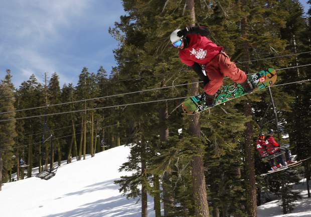 A snowboarder reaches for a grab during jam-formatted competition at Sierra-at-Tahoe.