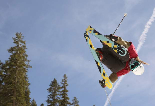 A skier reaches for a double grab airing off a terrain park feature during competition at Sierra-at-Tahoe.