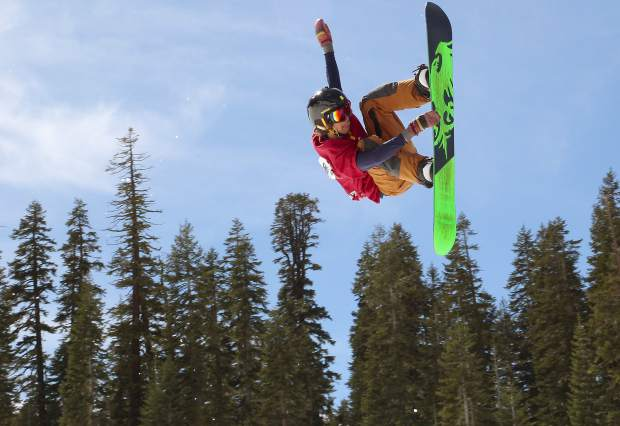A snowboarder reaches for a grab during a competition at Sierra-at-Tahoe.