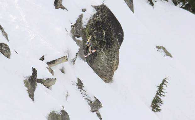 A snowboarder reaches for a grab during a cliff drop Friday.