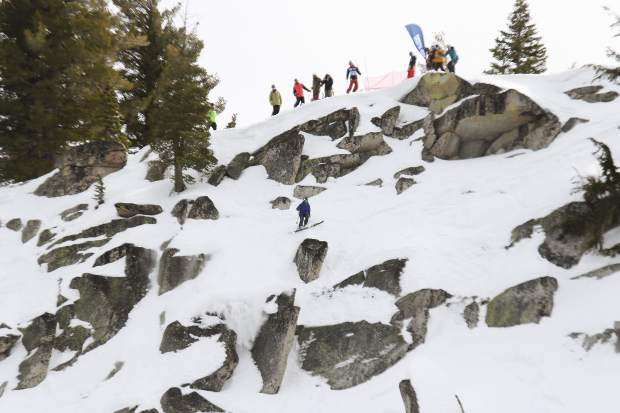 Competitors look on as a skier navigates towards a drop in Huckleberry Canyon.