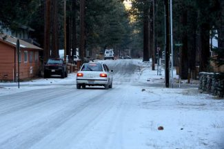 A car drives down a snowy South Lake Tahoe road Wednesday.
