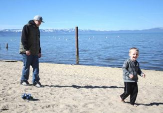 Jesse Chulay, right, and Landon Listner enjoy a sunny day Tuesday on a South Lake Tahoe beach. The weather has been mostly dry lately, but two storms are expected in the area by the end of the week.