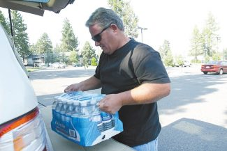 Adam Jensen / Tahoe Daily TribuneConcord resident Don Morrison, 51, loads a case of bottled water into his car at the South Lake Tahoe Safeway on Tuesday evening.