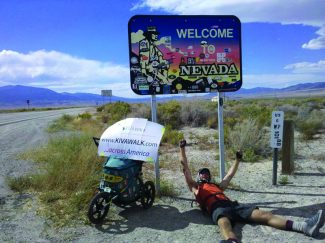 """Provided to the TribuneJonathon Stalls takes a rest in front of the """"Welcome to Nevada"""" sign on his trek across the United States to raise awareness for Kiva, a microlending platform that currently works with 54 countries across the globe."""