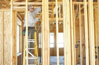 Shannon Litz / Nevada AppealDon Schmidlin of Hettrick Electric works on wiring a house on Friday afternoon. The team behind the development said they have found a niche market for customs homes that has helped them buck the trend and build houses in a down market.