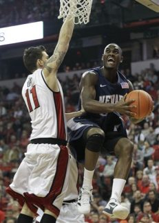 Nevada's Malik Story, right, goes up for a shot against UNLV's Carlos Lopez in the first half of an NCAA college basketball game, Monday, Nov. 14, 2011, in Las Vegas. (AP Photo/Julie Jacobson)